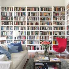 How to make a small room look bigger can be achieved by adding a floor-to-ceiling or wall-to-wall bookcase. This trick will expand how high your ceilings look, plus it's a great way to add storage.