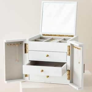 10 Jewelry Boxes to Keep Your Precious Jewels Organized include Size: 10 x 10 inches | 6 compartments | 10 hooks | Box Material: Engineered wood with a lacquered finish | Lining Material: Velvet It's difficult to beat a classic! With a white lacquer finish and twin doors, this jewelry box from West Elm is timeless, yet it also holds everything you need to store a modern jewelry collection. There are numerous compartments with space to hang necklaces, velvet-lined drawers to hide away miscellaneous items, cushioned ring slots, and a mirrored top. We particularly adore the dazzling asymmetrical metal accents, which add a great modern touch. To all of you lovely items, consider it home sweet home.